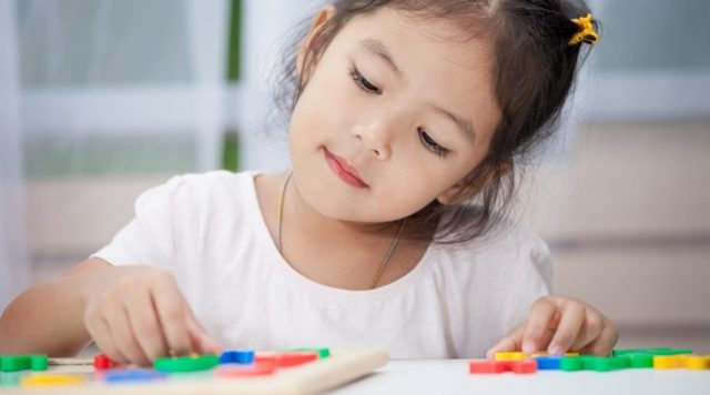 Cute little child girl having fun to play and learn magnetic alphabets on board