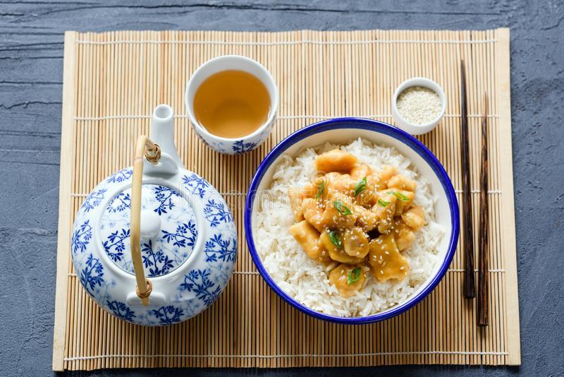 κινεζικό κοτόπουλο με το ρύζι chopsticks και πράσινο τσάι στο φύλλο μπαμπού 111867263