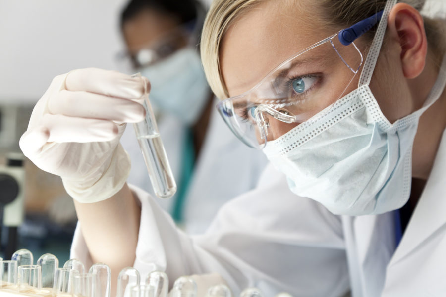 Female Scientific Research Team With Clear Solution In Laboratory